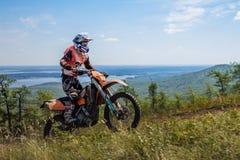 Катание мотоциклиста спортсмена на горе в предпосылке гор и озера Стоковые Изображения