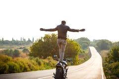 Катание молодого человека на мотоцилк, делая фокусы на дороге сельской местности Стоковое фото RF