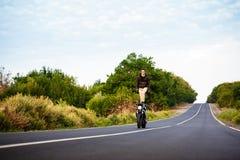 Катание молодого человека на мотоцилк, делая фокусы на дороге сельской местности Стоковая Фотография