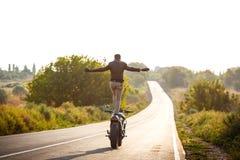 Катание молодого человека на мотоцилк, делая фокусы на дороге сельской местности Стоковые Фото