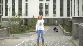 Катание молодой женщины в парке на электрическом самокате экологический переход видеоматериал