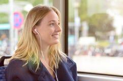 Катание молодой женщины в шине слушая к музыке Стоковое фото RF