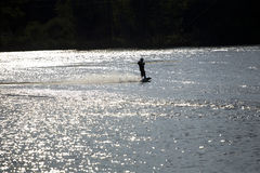 Катание на водных лыжах в заходе солнца Стоковые Изображения