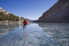 Катание на коньках человека на замороженном озере гор стоковые изображения