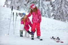 Катание на лыжах, мать зимы потех-усмехаясь подготавливая для катаясь на лыжах дочери Стоковые Изображения