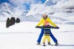 Катание на лыжах семьи в горах Лыжа матери и ребенк стоковое фото rf