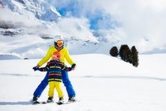Катание на лыжах семьи в горах Лыжа матери и ребенк стоковые изображения