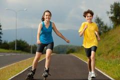 Активное молодые люди - rollerblading, skateboarding Стоковые Фотографии RF