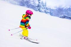 Катание на лыжах маленькой девочки в горах Стоковые Фото