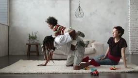 Катание ребенка смешанной гонки на задней части ` s отца дома видеоматериал