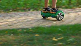 Катание ребенк на скутере гироскопа на дороге парка стоковая фотография rf