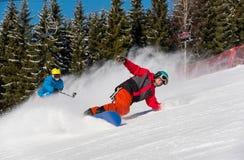 Катание Snowboarder в горах на солнечный зимний день Стоковое Фото