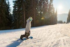 Катание Snowboarder в горах на солнечный зимний день стоковая фотография