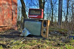 Катастрофа угрозой апоралипсическая Возможные последствия Отброс на улице Старые сломленные ТВ лампы, тостер и маска противогаза  стоковые изображения
