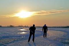 Кататься на коньках льда в Нидерландах на заходе солнца Стоковое Изображение