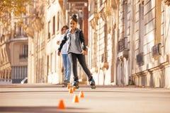 Кататься на коньках ролика девочка-подростка на прогулке города бортовой Стоковые Изображения