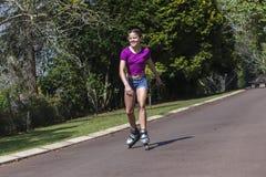 Кататься на коньках Rollerblade девушки стоковое фото