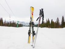 Кататься на лыжах против фона снег-покрытых подъема и лыжи Стоковые Изображения