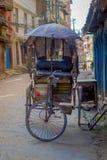 КАТМАНДУ, НЕПАЛ 15-ОЕ ОКТЯБРЯ 2017: Неопознанные люди в рикше в историческом центре города, в Катманду, Непал Стоковая Фотография