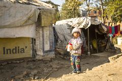 КАТМАНДУ, НЕПАЛ - плохой ребенок около их домов на трущобах в районе Tripureshwor Стоковые Фотографии RF