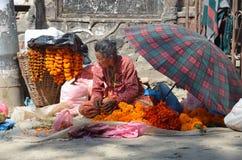 Катманду, Непал, 10-ое октября 2013, сцена непальца: Женщина продает ритуальные цветки на улице в Катманду Стоковая Фотография