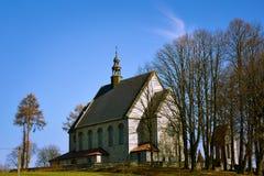 Католическая церковь на холме в сезоне осени с деревьями без листьев стоковая фотография