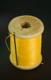 Катышка с желтым потоком и игла на черноте Стоковое фото RF