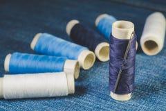 Катышкы белых и голубых потоков и шить иглы на джинсовой ткани стоковые изображения