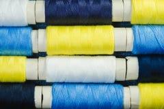 Катышкы голубого, желтого, и белого шить потока аранжированного в строках на джинсовой ткани стоковые фотографии rf