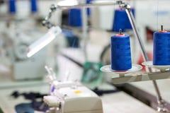 Катышкы голубых потоков на швейной машине, фабрике стоковое изображение rf