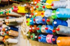 Катышкы красочного потока в шить студии Селективный фокус Красочная катышка потока вышивки использующ в швейной промышленности стоковые изображения