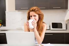 Кафе девушки Redhead выпивая в кухне Стоковая Фотография RF