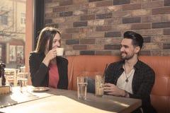 Кафе молодой женщины выпивая, человек смотря один другого, сторону к fa Стоковая Фотография RF