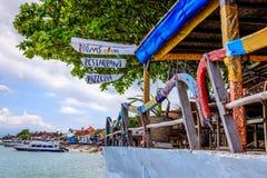 Кафе пляжа с аутриггерами от старых традиционных индонезийских шлюпок longtail как поручни Nusa, Lembongan, Индонезия Стоковые Изображения RF