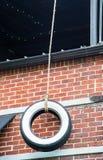 Качание автошины на кирпичной стене Стоковое фото RF