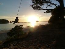 Качание веревочки восхода солнца ` s ребенка на пляже Стоковые Фотографии RF