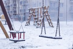Качание для детей в зиме спортивная площадка около дома стоковое изображение