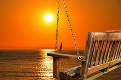 Качание с заходом солнца и парусником озера стоковое изображение
