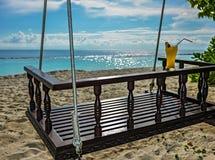 Качание с стеклом питья на тропическом пляже Стоковая Фотография