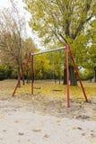 Качания в парке с желтыми упаденными листьями деревьев Стоковые Фотографии RF