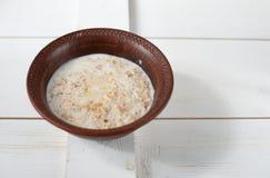 Каша гречихи с молоком, маслом, и свежей петрушкой в глубоком шаре Стоковая Фотография
