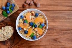 Каша овсов без сахара Каша с свежими tangerines, голубиками и фундуками в белом шаре и на деревянной предпосылке Стоковое Фото