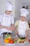 2 кашевара в кухне подготавливая Стоковые Изображения