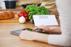 Кашевары женщины на кухне используя планшет Скопируйте зону космоса на сенсорной панели Здоровая еда, вегетарианская еда и Стоковая Фотография