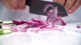 Кашевар быстро отрезал фиолетовый лук с ножом сток-видео