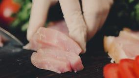 Кашевар в белых одеждах с крышкой режет мясо бекона сток-видео