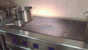 Кашевар в равномерной стойке покрыл лоток на работая плите на кухне ресторана варить тарелку подготовлять сток-видео