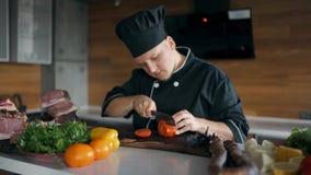 Кашевар в черных одеждах с крышкой режет томат видеоматериал