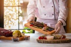 Кашевар держит доску с мясом Стоковое Изображение