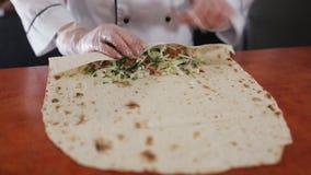 Кашевар женщины в ресторане обочины подготавливает Shawarma сток-видео